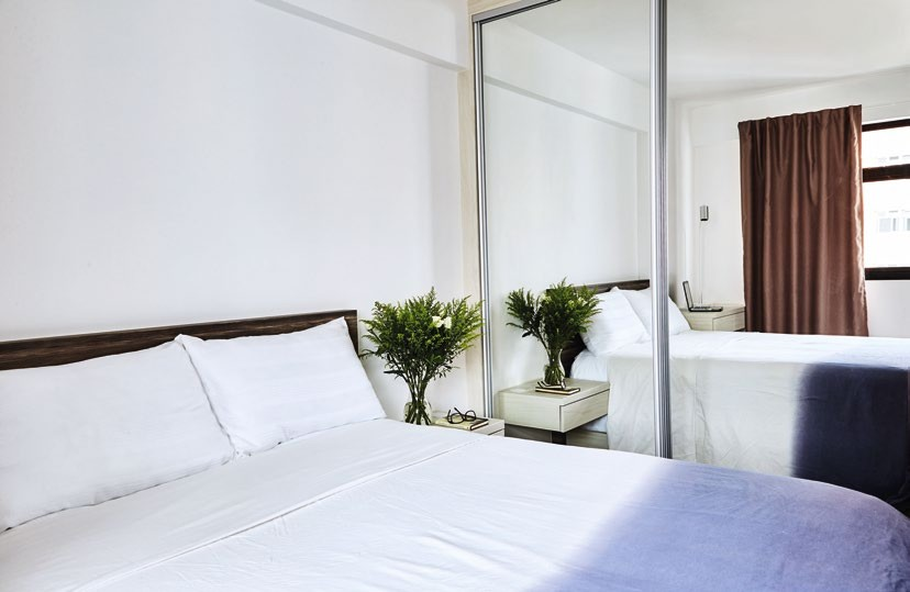 Full-height mirrored doors were used for the master bedroom's wardrobe to make the space look bigger.