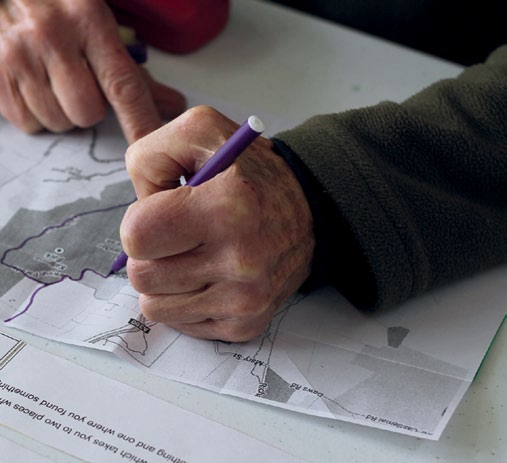 A participant tracing their memories at Lines We Might Have Walked.