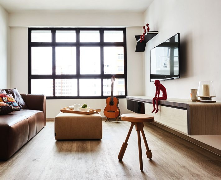 The furniture's placement and the vinyl floor tiles, from Tarkett, follow the same linearity to visually elongate the living room. Red figurines, from Ode to Art.