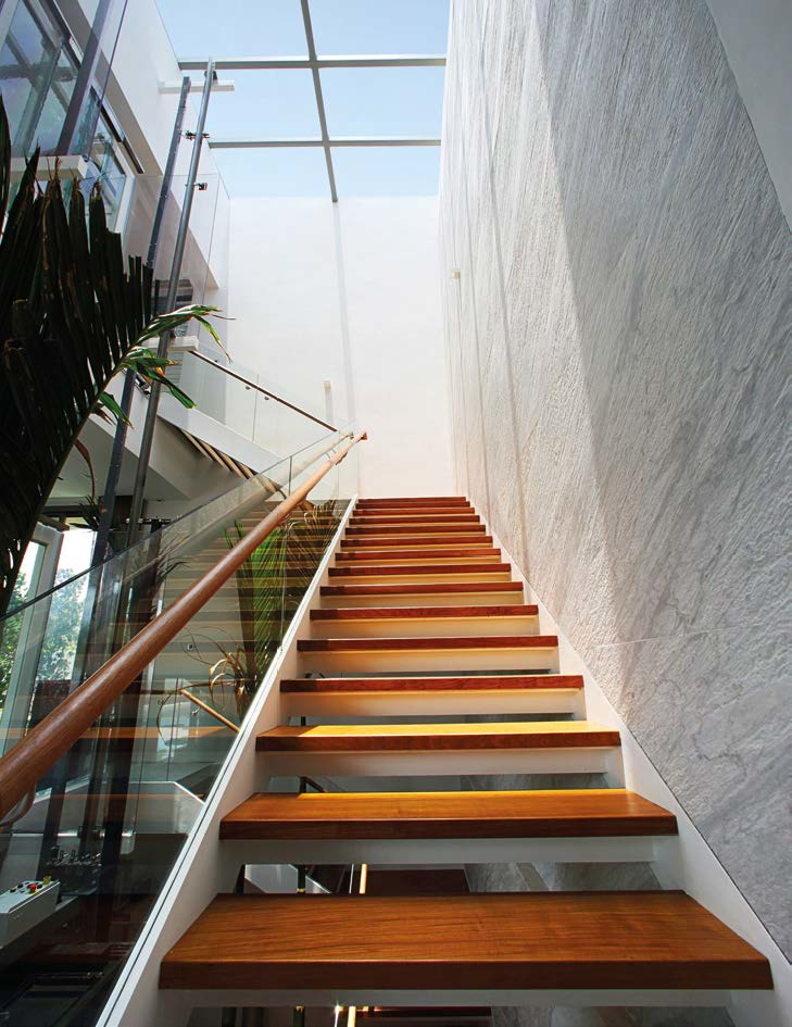 Acid etching on the light grey marble feature wall along the staircase gives it a leathery texture.