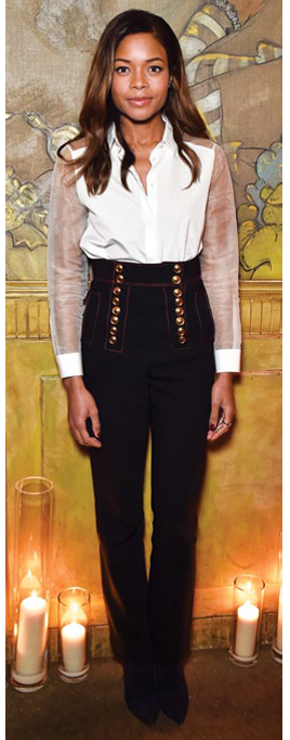 Naomie Harris pairs a sheer white button down with high-waisted pants.