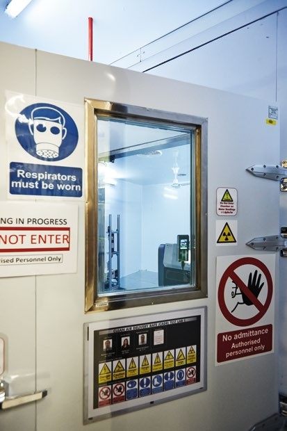 The CADR test lab is slightly radioactive; a charge neutralizer uses a radioactive isotope to remove charge from dust, preventing it from sticking to the lab's metal walls.