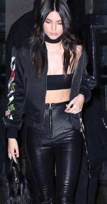 Kendall Jenner in an Off-White bomber jacket with signature white stripes.