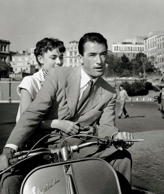 Audrey Hepburn and Gregory Peck make  their way around the city on a Vespa in Roman Holiday.