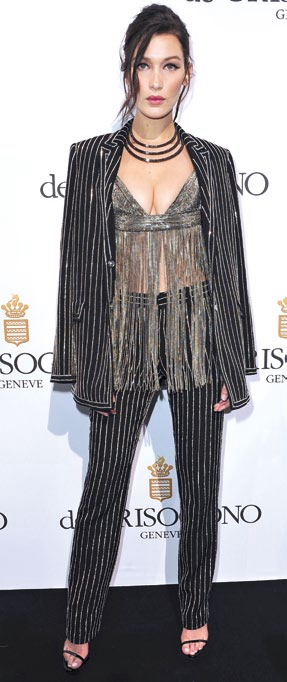 Bella Hadid matches her metallic pinstripe suit with a metallic fringed top.