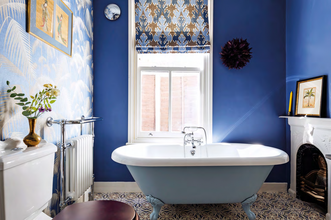 The wallpaper by Cole & Son, West Bengal blind fabric by Kelly Wearstler, and 19th-century Japanese silk paintings from the Rowley Gallery in Kensington add drama to the bathroom.