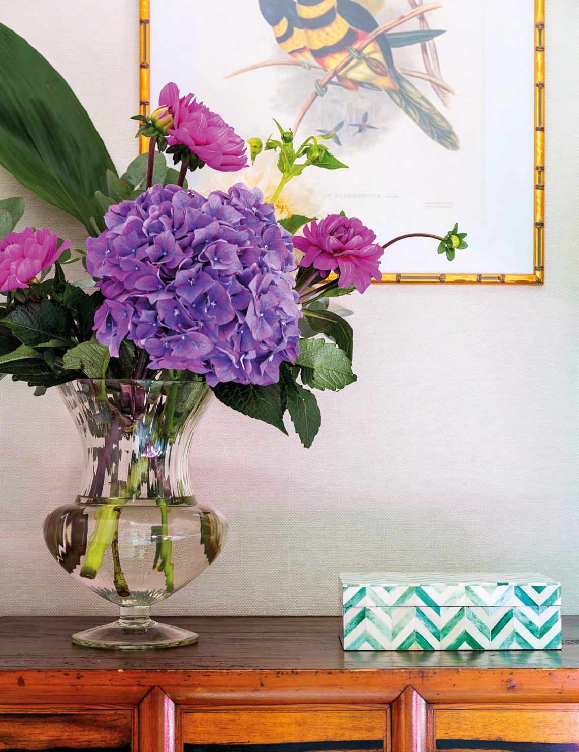 The vibrant colours of the floral arrangement accentuate the jewel tones of the master bedroom.