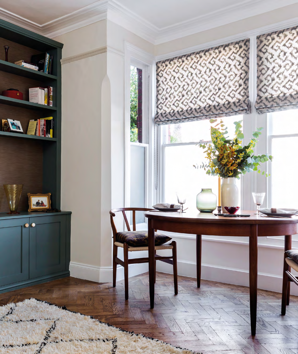 The dining area is an extension of the living room. The Askha blind fabric by Jim Thompson picks up on the Farrow & Ball Green Smoke paint used on the cabinets.