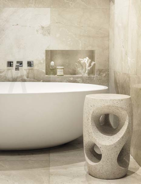 In the master bathroom, the walls and floor are from Opus Stone, the bathtub is by Apaiser, the faucets are from Dornbracht and the side table is by Oly Studio.