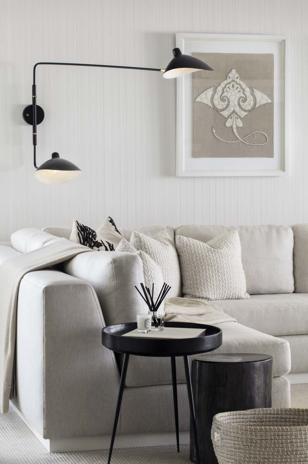 In the living room, a sconce by Serge Mouille contrasts with the Phillip Jeffries wallpaper. The side tables are by Fineline (petrified wood) and Mater. The sofa was customised with a Dedar fabric.