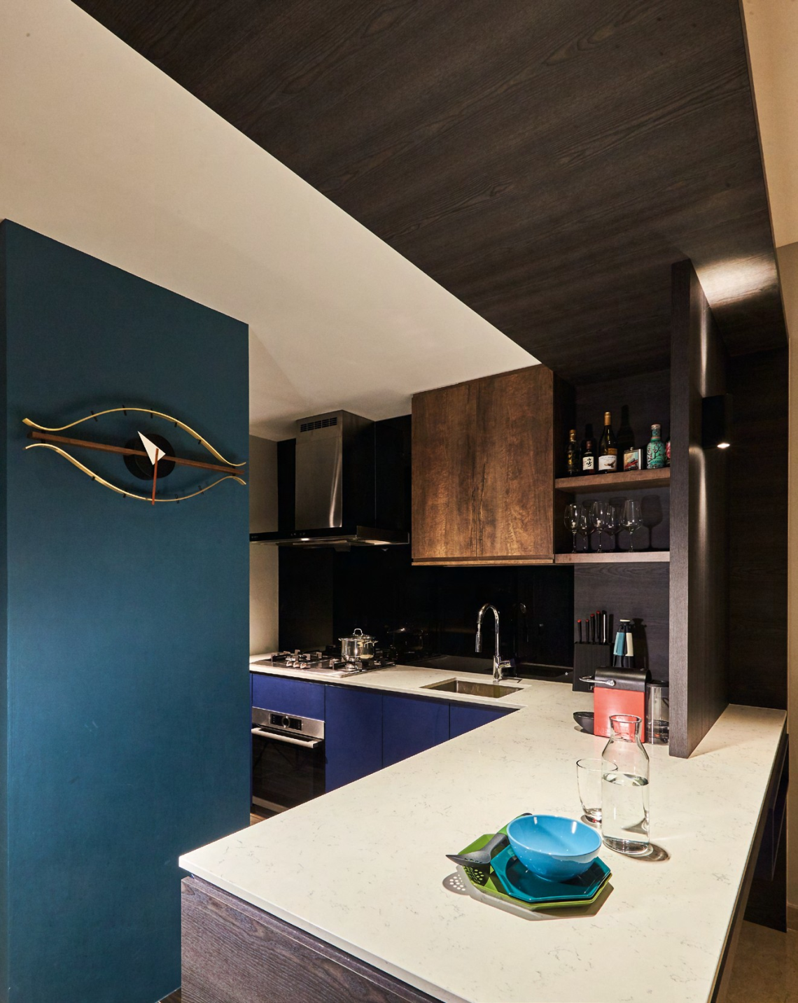 Joey replaced the original floor tiles with wooden tiles in a colour similar to American Walnut, which complements the dark blue laminates of the kitchen cabinets.