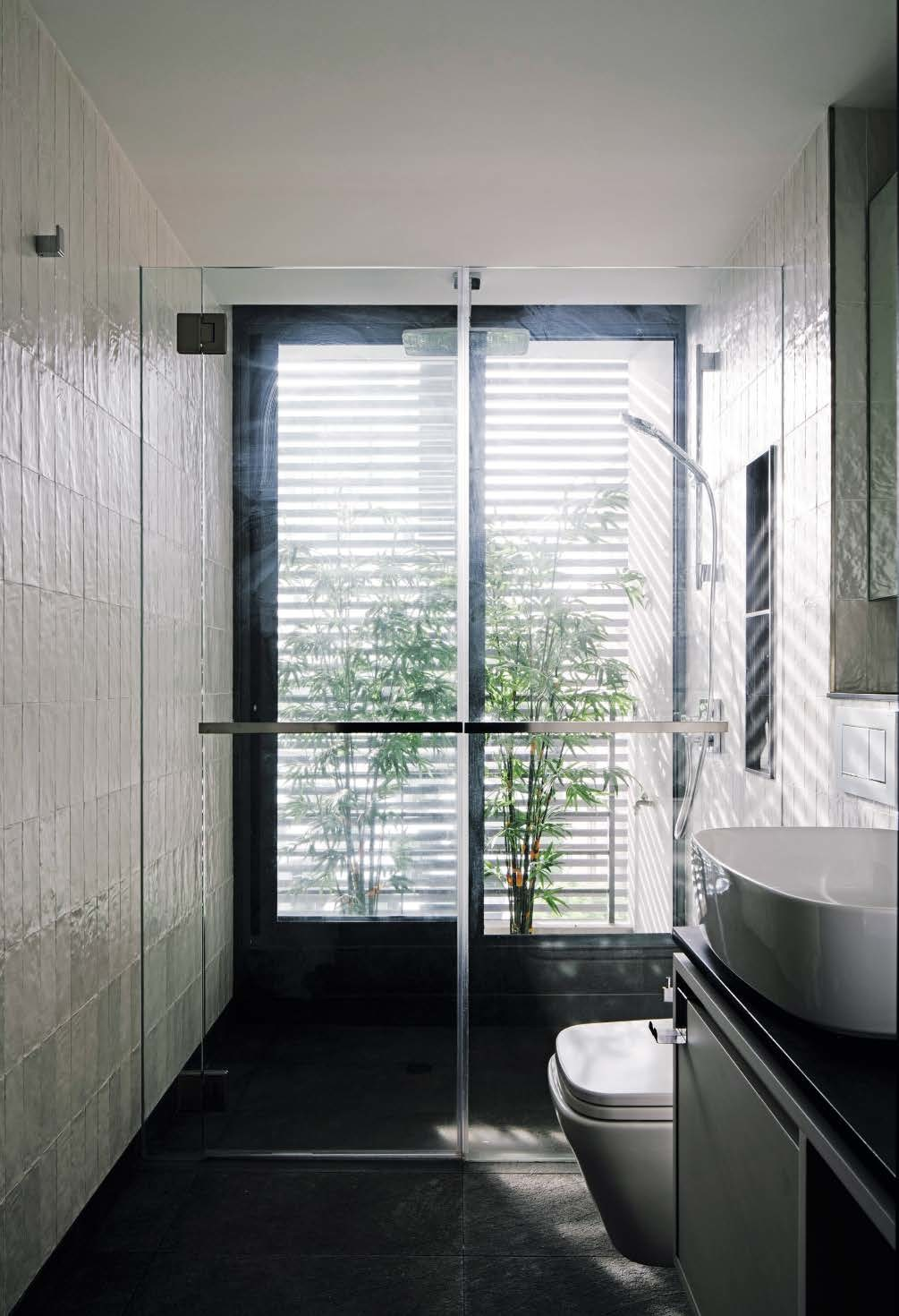 The screens on the building facade, together with the bamboo plants beside the shower, filter the light entering the master bath and create an interesting play of light and shadow.