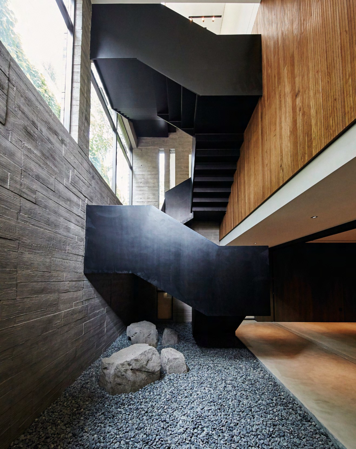 A staircase constructed out of folded black sheet metal takes centre stage within the double volume space, and serves as a sculptural expression of vertical circulation.