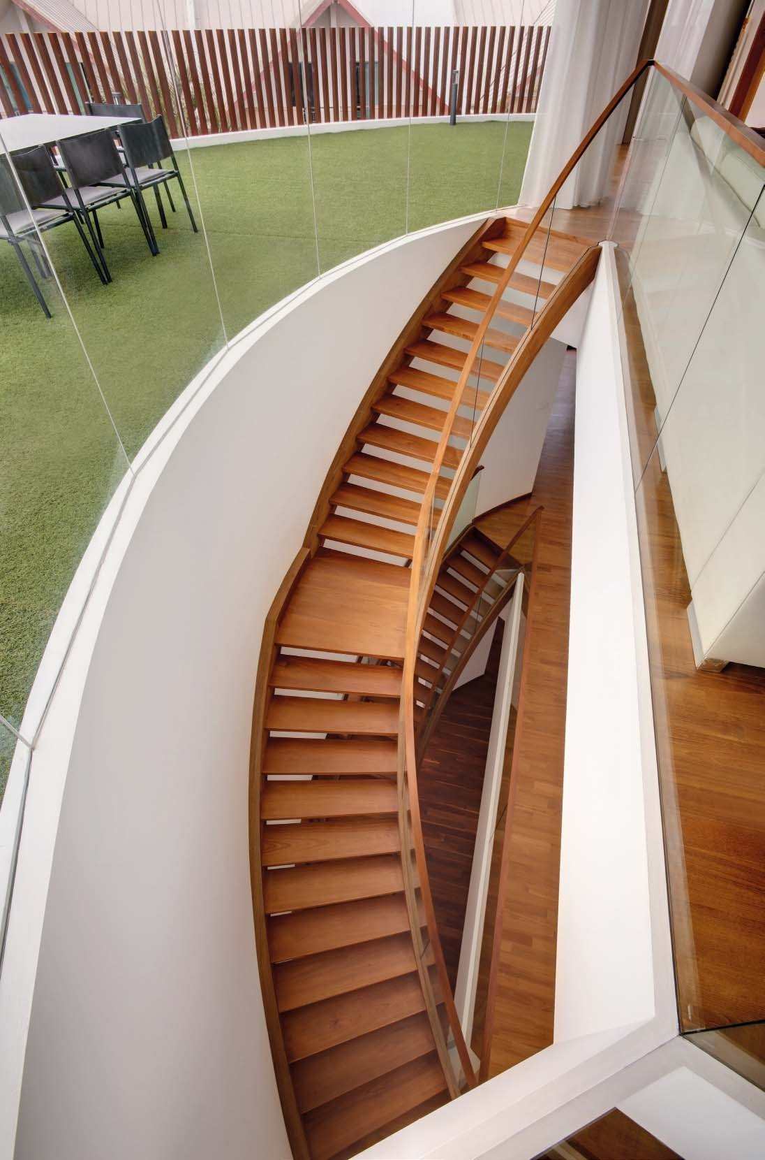 """The elegance, lightness and porosity of the curved staircase, constructed of mild steel and with timber veneer cladding, complements the """"floating"""" quality of  the house."""