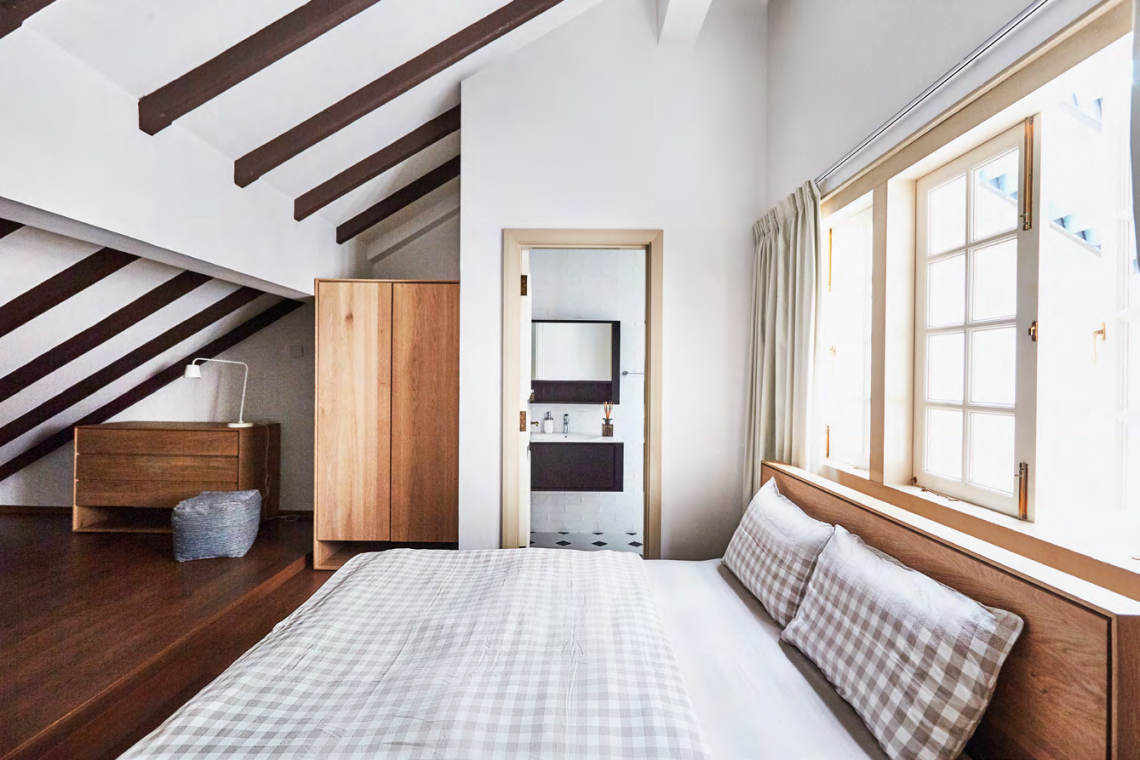 The sloping roof gives the guest room on the third storey a unique character. It overlooks the air well, which brings in natural light for an airy and welcoming feel.