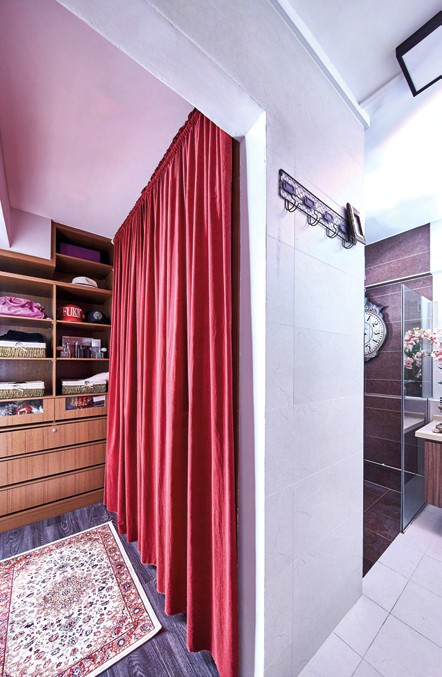 Customised fullheight shelves  were added in the  master bedroom  to keep the space  looking clutterfree. Curtains in  maroon hues,  paired with rugs  in the room,  offer both a bold  look and a cosy  ambience.