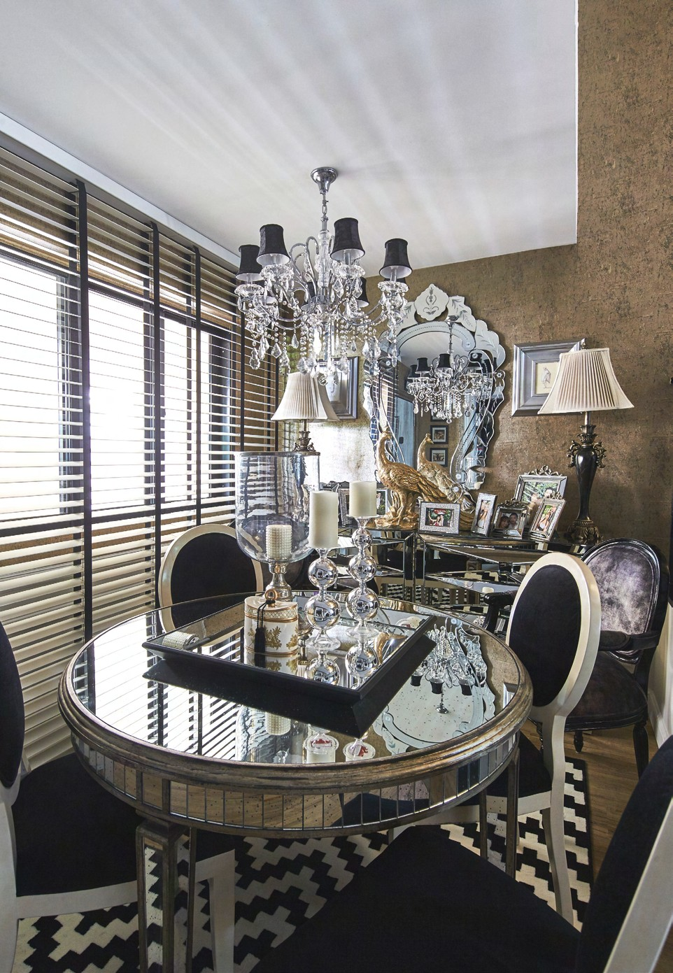 The dining room sits right by the entrance, and enjoys natural light from the common corridor outside. The light is also reflected off the mirrored surfaces of the dining table, which is complemented by black-and-white round-back chairs. Behind, a sideboard filled with the couple's photos and knick-knacks give the home a personal touch.