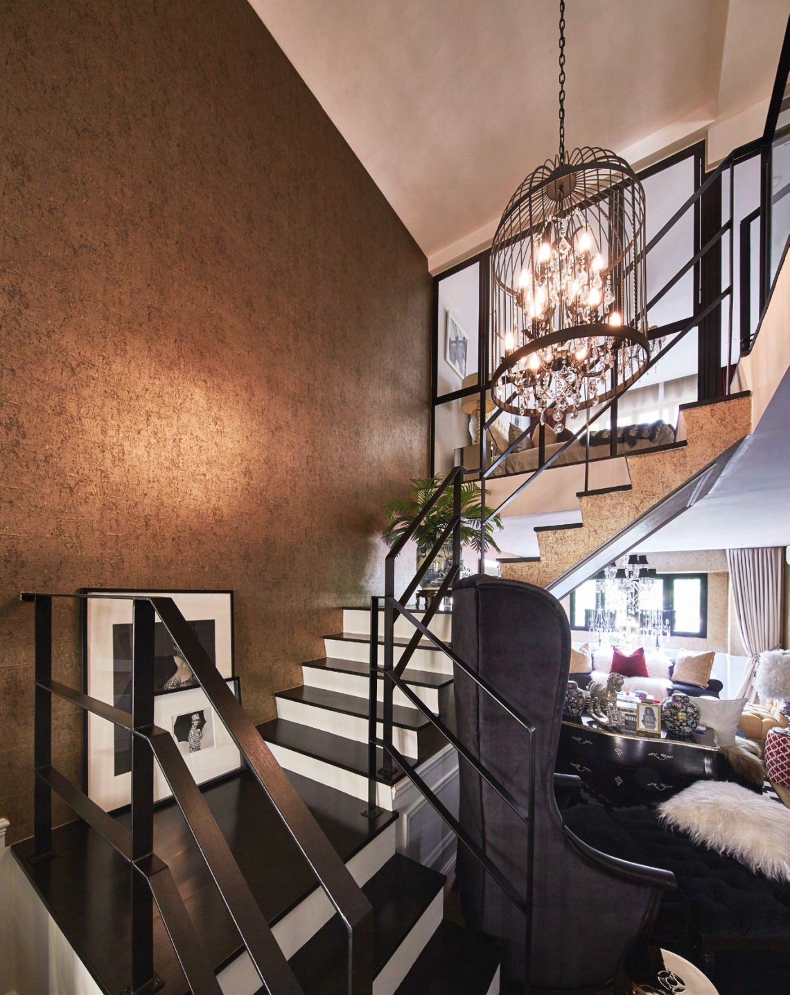 As advised by their fengshui master, the couple clad the walls in their home with gold textured wallpaper. A bird cage-inspired chandelier hangs by the staircase and creates an attractive focal point.